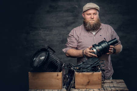 The fat bearded hipster male holds vintage 8 mm video camera and colorful soffits lamps. Stock Photo