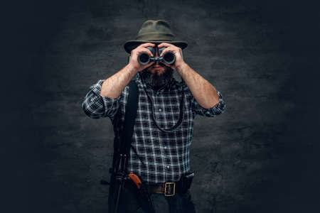 Studio portrait of bearded hunter male wearing a plaid fleece shirt looking through binoculars, holds a rifle.