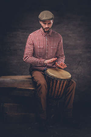 Studio portrait of a man plays on ethic wooden drums. Stock Photo