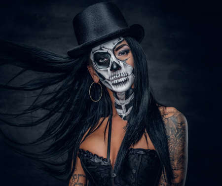 Portrait of zombie woman with painted skull face.