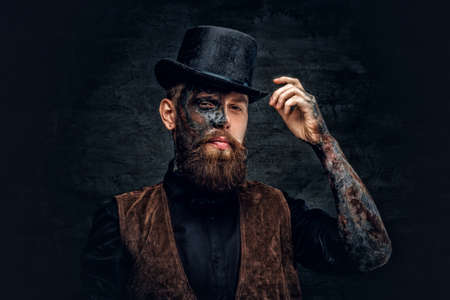 Portrait of a scary bearded male with burning make up and cylinder hat. Stock Photo