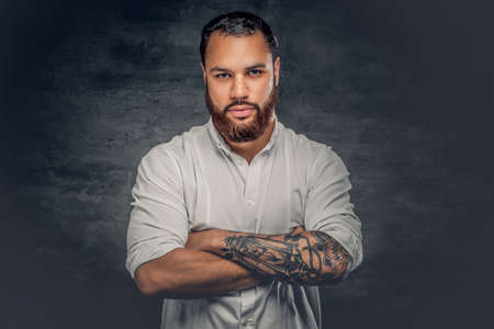 Positive bearded Black male with a tattoo on cross arms, dressed in a white shirt. Foto de archivo