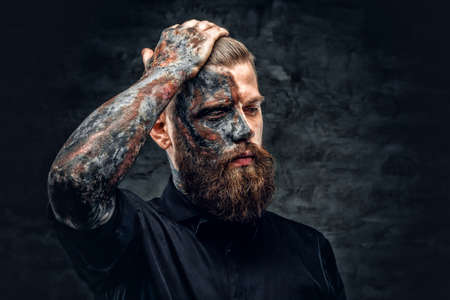 hellish: Portrait of a scary bearded male with burning make. Stock Photo