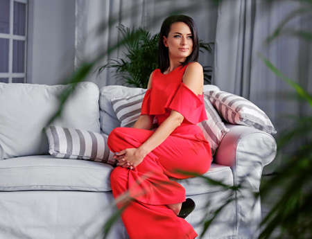 green couch: A brunette female dressed in a red evening dress sits on a coach in a room with green plants and grey interior.