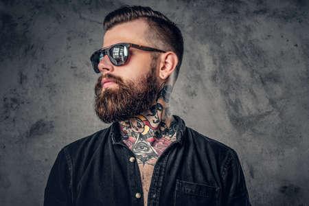 黒の t シャツとサングラスを着て彼の腕や首に入れ墨をしたひげを生やした流行に敏感な男のスタジオ ポートレート