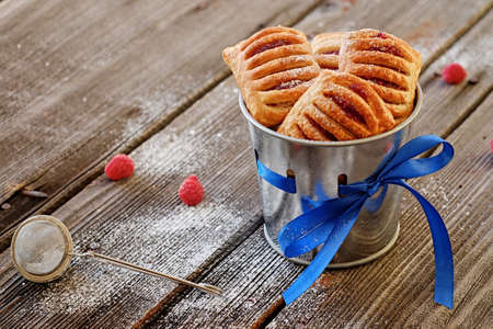 Three tasty dough cakes in a cup on a wooden table. Stock Photo