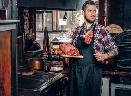 Portrait of a bearded chef with tattoos on his arms hold beef steak on a kitchen.