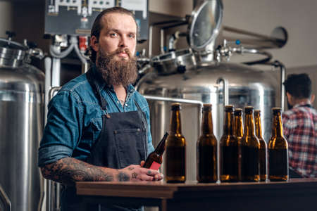 microbrewery: Tattooed bearded Caucasian and Indian men presenting craft beer in the microbrewery.
