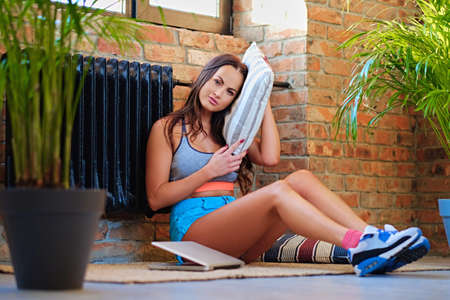 Attractive sporty brunette female sits on a floor after fitness workouts.