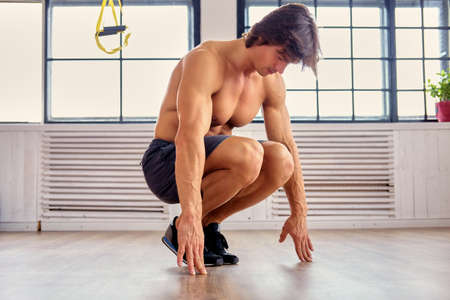 Full body portrait of muscular shirtless male doing workouts on a floor in a room with natural light. Stock Photo