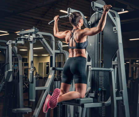 levantar peso: Female with short hair doing pull ups in a gym club.