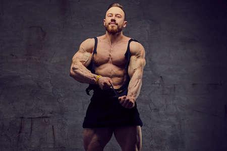 Portrait de bodybuilder barbu torse nu sur fond gris.