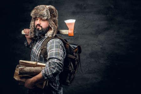 Portrét brutálního vousatého lovce muže oblečeného do fleece košile a klobouku z kožešiny má sekeru na rameni.