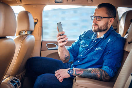 Stylish bearded male in eyeglasses with tattoo on his arm, talking by smart phone in a car. Reklamní fotografie