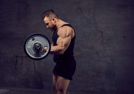 Un énorme bodybuilder barbu travaillant avec haltères.