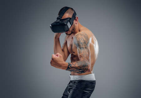 A shirtless, tattooed fighter with virtual reality glasses on his head isolated on grey background. Stock Photo