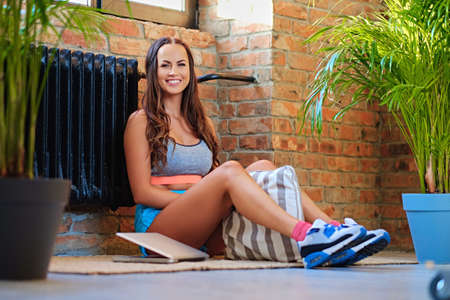 Full body portrait of sporty brunette female sits on a floor in a room with a wall of a brick.