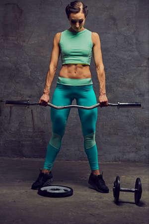 barbel: Full body portrait of sporty female dressed in an azure sportswear holds barbel.