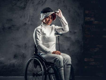 車椅子の女性剣士は、安全マスクおよび剣を保持します。