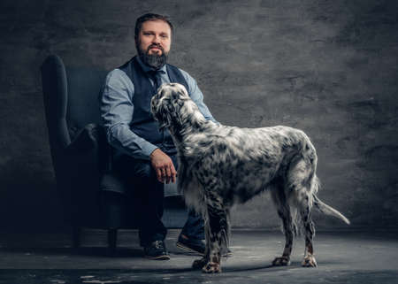 Portrait of stylish bearded male sits on a chair and the Irish setter dog.