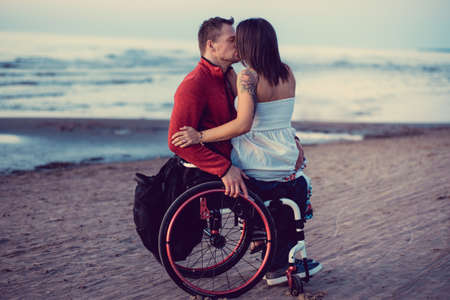 Handicapped young couple kissing on a beach. Reklamní fotografie - 74800927