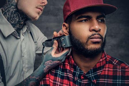 Schließen Sie herauf Porträt von tätowierten männlichen Friseurschnitten, Bart zu einem schwarzen Mann.