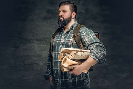 Fat bearded male holds fire woods over grey background.