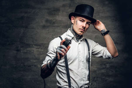 A man with tattoo on a face, dressed in a white shirt and a cylinder hat holds hair trimmer. Stock Photo