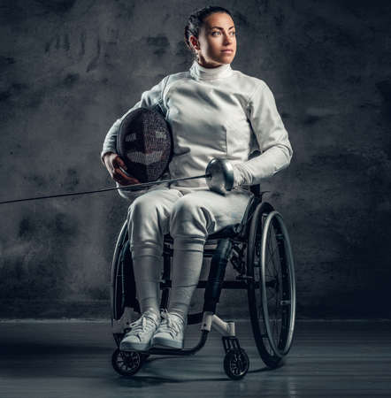 Female fencer in wheelchair holds safety mask and a sword.