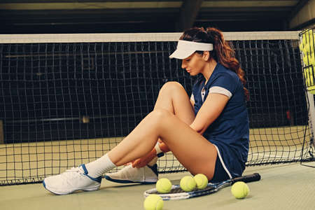 Full body portrait of brunette female tennis player posing on a ground in a court.
