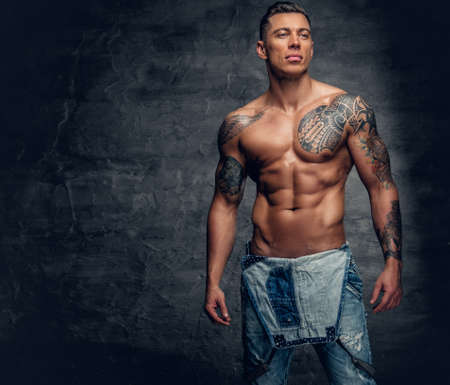 Studio portrait of handsome muscular male fitness model with tattoo on a chest dressed in a jeans. Reklamní fotografie