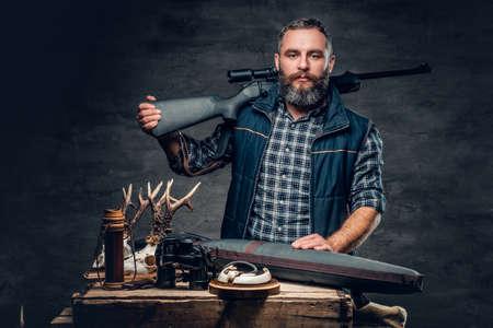 彼のトロフィーとひげを生やした近代的なハンターのスタジオの肖像画は、ライフルを保持しています。 写真素材