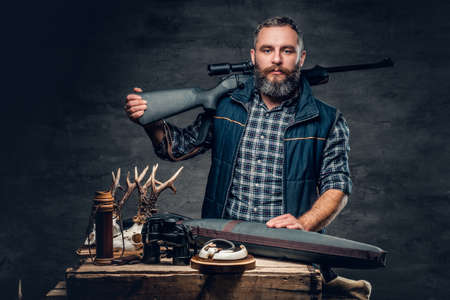 Studio portrait of a bearded modern hunter with his trophy holds a rifle. Banco de Imagens - 75508538