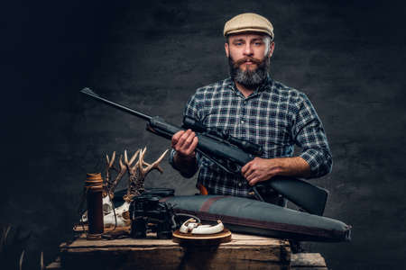 Studio portrait of a bearded traditional hunter with his trophy holds a rifle. Reklamní fotografie