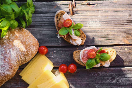 Brown bread with ham, basil and tomatoes on a grey wooden table.