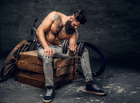 throttle: Shirtless bearded male with tattooed torso sits on a wooden box and holds dumbbell.