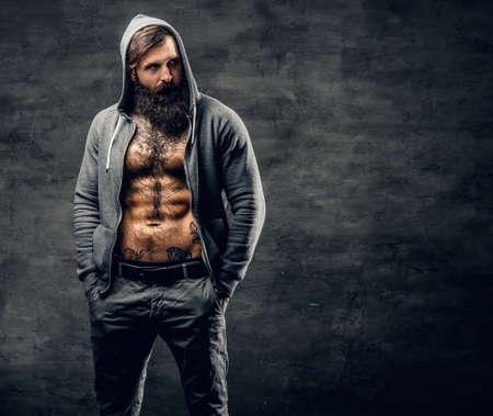 Portret van brute bebaarde man met tatoeage op een kist, gekleed in een grijze hoodie.