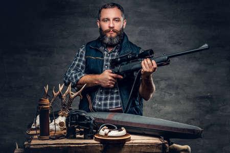 Studio portrét vousatého moderního lovce se svou trofejí drží pušku.