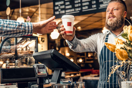 Positive bearded barista male selling coffee to a consumer in a coffee shop. Stock Photo