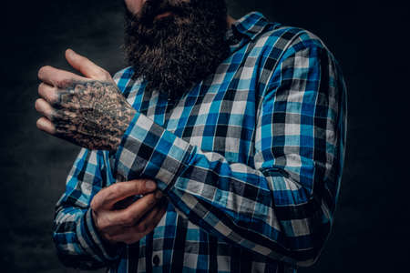 Bearded male with a tattoo on his arm dressed in a blue fleece shirt. Close up