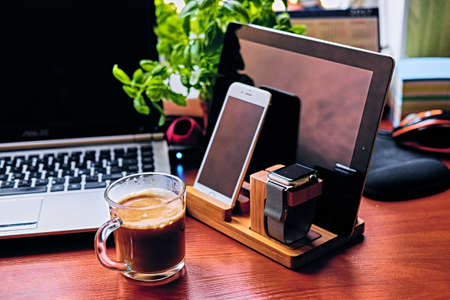 Communication set with smart watch, tablet PC, computer and a cup of coffee on a table.