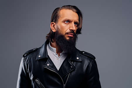 Portrait of bearded male with long hair dressed in a black leather jacket.