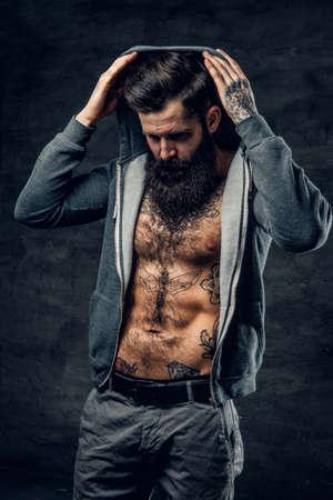 throttle: Studio portrait of athletic bearded male in a grey hoodie.