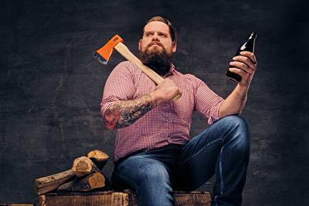 lumberjack shirt: Bearded lumberjack male with tattoos on arms, sits on a wooden box and holds the axe and beer bottle. Stock Photo