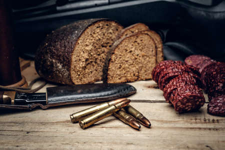 Delicious sausage, brown bread and gun cartridge on a wooden table. Stock Photo