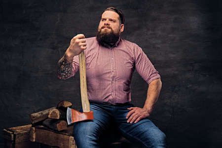 lumberjack shirt: Bearded lumberjack male with tattoos on arms, sits on a wooden box and holds the axe.