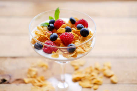 Gold crunchy corn flakes with some wild berries in a glass cup. Stock Photo