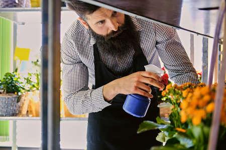 Tattooed bearded male watering flowers in a market shop.
