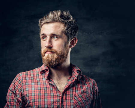 haircut: Studio portrait of blond bearded male dressed in a red fleece shirt over dark grey background.