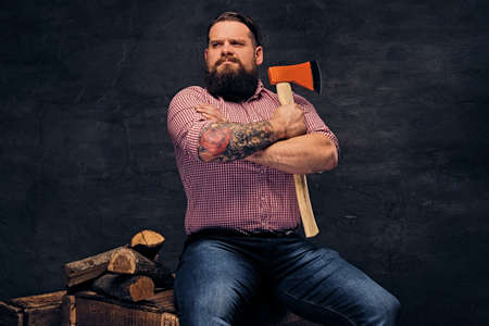 lumberjack shirt: A bearded lumberjack with tattoo on arms, dressed in a pink fleece shirt holds the axe.